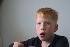 Ung röd haired pojke vid frukosten royaltyfri foto