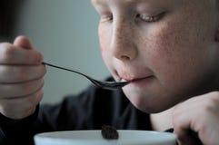 Ung röd haired pojke vid frukosten arkivfoton