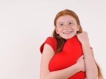 Ung röd kram för hårflicka ömt en hjärtaform på grå bakgrund Arkivbild