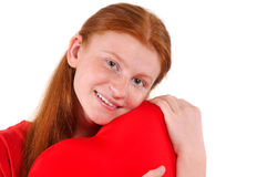 Ung röd kram för hårflicka ömt en hjärtaform på vit bakgrund Fotografering för Bildbyråer
