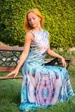 Ung röd kvinna på en bänk Royaltyfria Foton