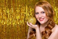 Ung rödhårig flicka på en guld- bakgrund Arkivfoto