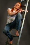 Ung rödhårig flickabenägenhet på en stege Arkivfoton