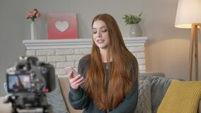 Ung rödhårig flickablogger och att le och att tala på kameran, genom att använda en smartphone som läser kommentarer, hemkomfort  lager videofilmer