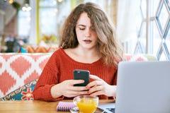 Ung rödhårig fräknig flicka med två händer som rymmer en smartphone med ett förvånat uttryck royaltyfria foton