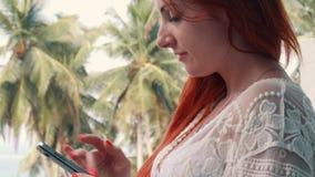 Ung rödhårig kvinna som använder telefonen på terrass i tropiskt land stock video