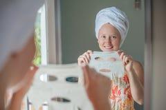 Ung rödhårig kvinna som gör det ansikts- maskeringsarket Arkivfoton