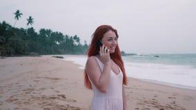Ung rödhårig kvinna som talar på telefonen på en tropisk strand lager videofilmer