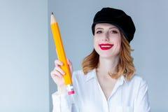 Ung rödhårig mankvinna i hållande chugeblyertspenna för hatt Arkivfoto