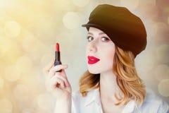 Ung rödhårig mankvinna i hatt med läppstift för makeup Royaltyfria Bilder