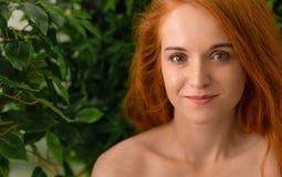 Ung rödhårig mankvinna som trycker på hennes framsida, grön bakgrund arkivfoto
