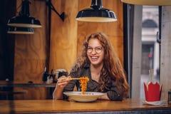 Ung rödhårig mankvinnlig som äter kryddiga nudlar i en asiatisk restaurang arkivbilder