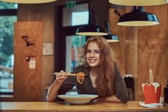 Ung rödhårig mankvinnlig som äter kryddiga nudlar i en asiatisk restaurang arkivfoto