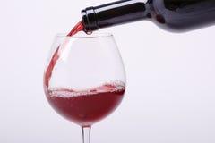 Ung rött vin hälls in i ett exponeringsglas Royaltyfria Foton