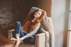 Ung readheadkvinna som hemma kopplar av i hemtrevlig stol, iklädd tillfällig tröja och jeans Arkivfoto