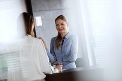 Ung receptionist som i regeringsställning talar med affärskvinnan Arkivfoton