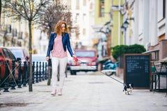 Ung redhaired Caucasian kvinna som promenerar den europeiska gatan med den lilla Chihuahuaavelhunden av två färger på koppeln Mol Arkivfoto