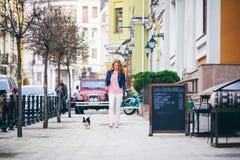 Ung redhaired Caucasian kvinna som promenerar den europeiska gatan med den lilla Chihuahuaavelhunden av två färger på koppeln Mol Arkivfoton