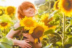 Ung redheaded kvinna i f?ltet av solrosor som rymmer en enorm grupp av blommor i en solig sommarafton royaltyfria bilder