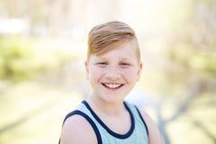 Ung redheaded pojke som utanför spelar arkivbilder