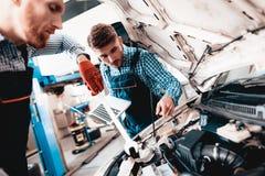 Ung reparationsbil för automatiska mekaniker med en skiftnyckel arkivbilder