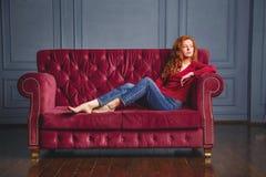 Ung rik kvinna som ligger på den röda soffan royaltyfri fotografi