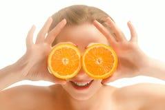 Ung rolig kvinna med orange skivor Fotografering för Bildbyråer
