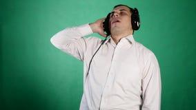 Ung rolig man med hörlurar på chroma stock video