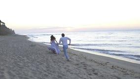 Ung romantiker enloved par - den nätta flickan i lång ljus klänning och stilig man kör playfully längs coastine på sandigt arkivfilmer