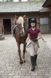 Ung ryttare med en ponny i den stabila gården Fotografering för Bildbyråer