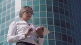 Ung säker affärskvinna som ser fotografierna i minnestavlan och tänker vilka intriger att välja lager videofilmer