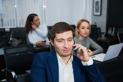 Ung säker affärsman som talar vid telefonen på kontoret Royaltyfri Bild