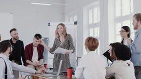 Ung säker härlig blond framstickandekvinna som talar till kollegor på det moderna ljusa kontoret som möter RÖD EPOS för ultrarapi lager videofilmer