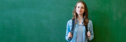 Ung säker le kvinnlig högstadiumstudent som framme står av den svart tavlan i klassrum och att bära en ryggsäck fotografering för bildbyråer