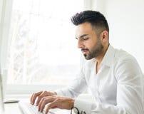 Ung säker man som arbetar i modernt kontor Royaltyfria Foton