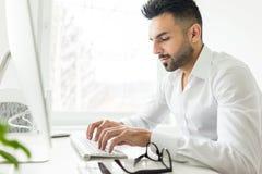 Ung säker man som arbetar i modernt kontor Arkivbild