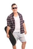 Ung säker man som rymmer en skateboard Arkivbild