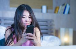 Ung sötsak och härlig asiatisk kinesisk 20-tal eller 30-talkvinna som ler lyckligt ligga på säng genom att använda internetmobilt Fotografering för Bildbyråer
