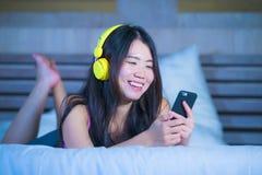 Ung sötsak och lycklig asiatisk kinesisk 20-talkvinna som lyssnar till musik Royaltyfri Bild