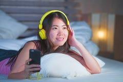 Ung sötsak och lycklig asiatisk kinesisk 20-talkvinna som lyssnar till musik Arkivfoton