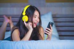 Ung sötsak och lycklig asiatisk kinesisk 20-talkvinna som lyssnar till musik Royaltyfri Fotografi