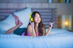 Ung sötsak och lycklig asiatisk kinesisk 20-talkvinna som lyssnar till musik Royaltyfria Bilder