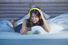Ung sötsak och lycklig asiatisk kinesisk 20-talkvinna som lyssnar till musiksången med hörlurar hörlurar med mikrofon och mobilte Royaltyfria Foton
