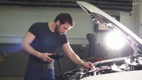 Ung service för motor för teknikermandanande av bilen i garage lager videofilmer