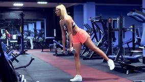 Ung sexig blond flicka i göra för idrottshall som är satt med hanteln arkivfilmer