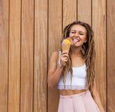 Ung sexig blond flicka med fruktaner som äter mångfärgad glass i dillandekottar i den varma aftonen för sommar som visar tungan,  Arkivbilder