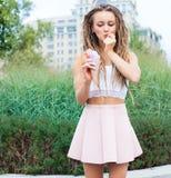 Ung sexig blond flicka med fruktaner som äter mångfärgad glass i dillandekottar i sommarafton, glat och gladlynt Europea Royaltyfria Bilder