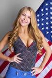 Ung sexig blond kvinna på amerikanska flagganbakgrund arkivfoton
