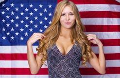 Ung sexig blond kvinna på amerikanska flagganbakgrund arkivbild
