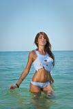 Ung sexig brunettflicka i den vita bikinin och våta t-skjortan som spelar i vattnet Royaltyfri Fotografi